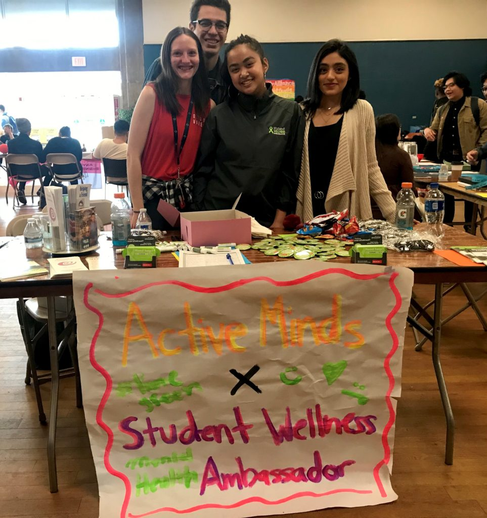 Student Wellness Ambassadors standing and smiling behind event table