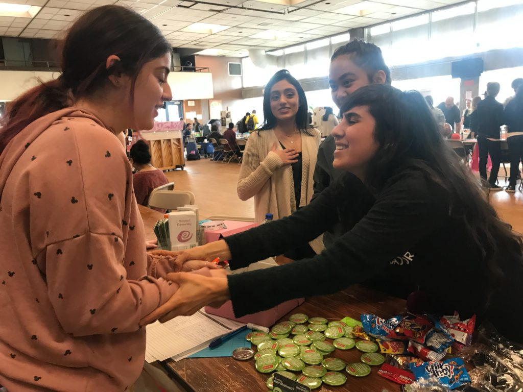 Student Wellness Ambassadors greet a fellow student across an event table